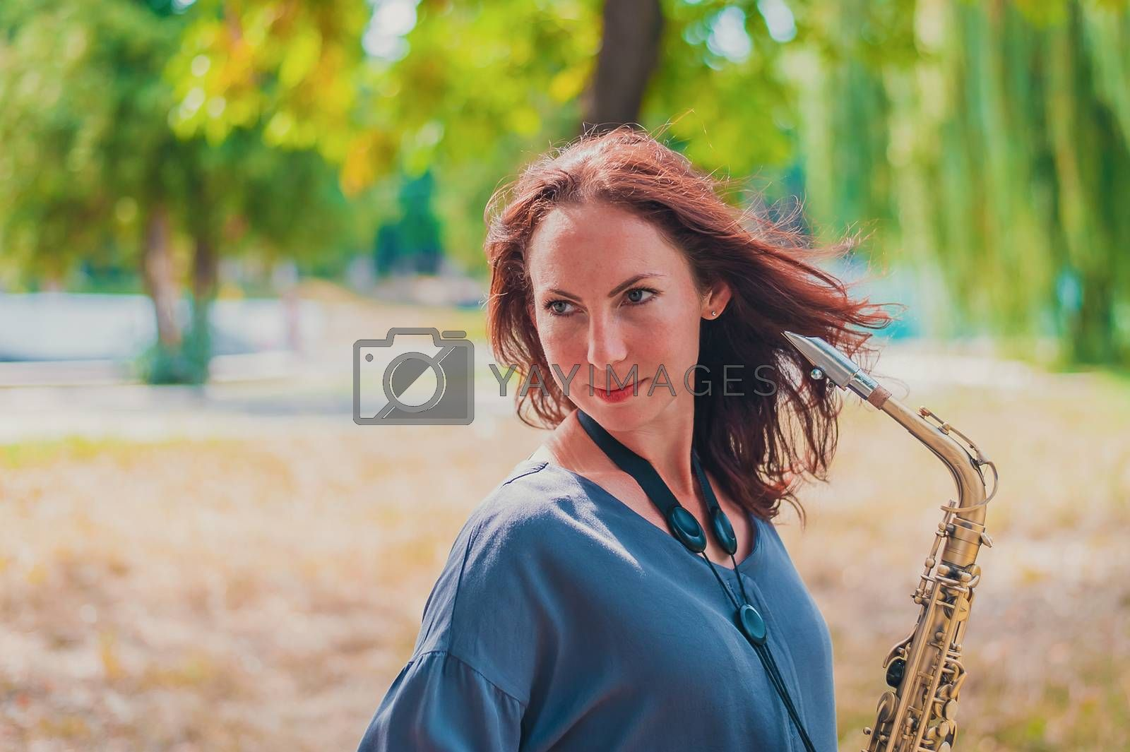 Close portrait of a young red-haired woman in a green park with a saxophone
