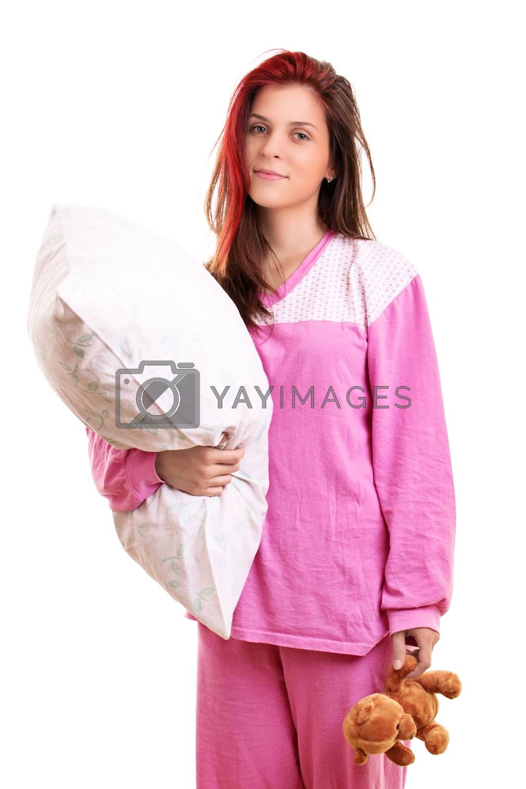 Beautiful smiling young girl in pink pajamas holding a pillow and a teddy bear, preparing to go to sleep, isolated on white background. Sleep and relaxation concept.