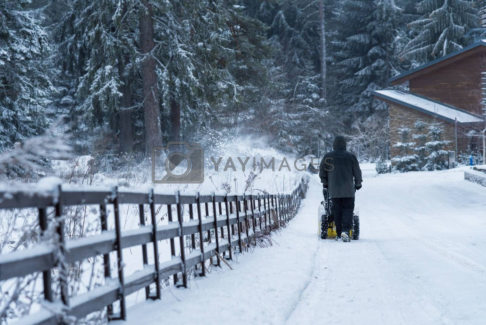 Man clears snow with snowblower after winter snowfall. by ba11istic