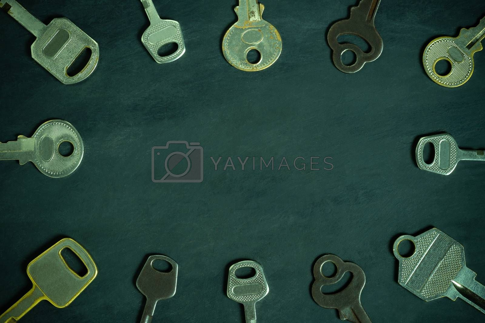 Different variety of vintage keys placed around in circular pattern on wooden background. Copy space in middle. Idea for keys to solving business problems to success. Concept for security or privacy.