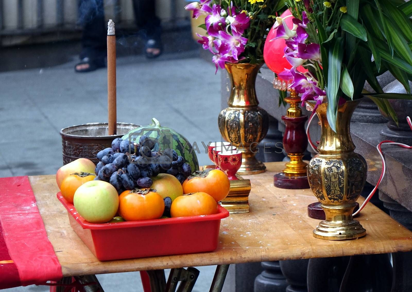 Buddhist worship table with fruits, wine, incense and flowers