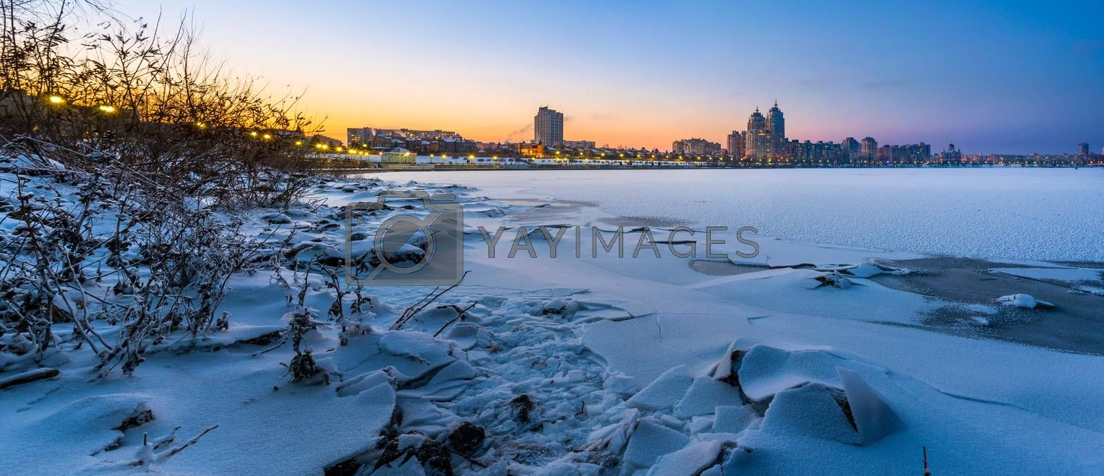Cold Winter night cityscape with illuminated buildings in Kiev, Ukraine. The frozen Dnieper river appears in the foreground