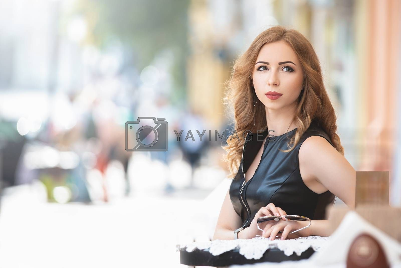 Attractive young caucasian glamour woman sitting in street cafe, waiting for someone, having coffee, having great time. She wearing black stylish dress, by Nickstock