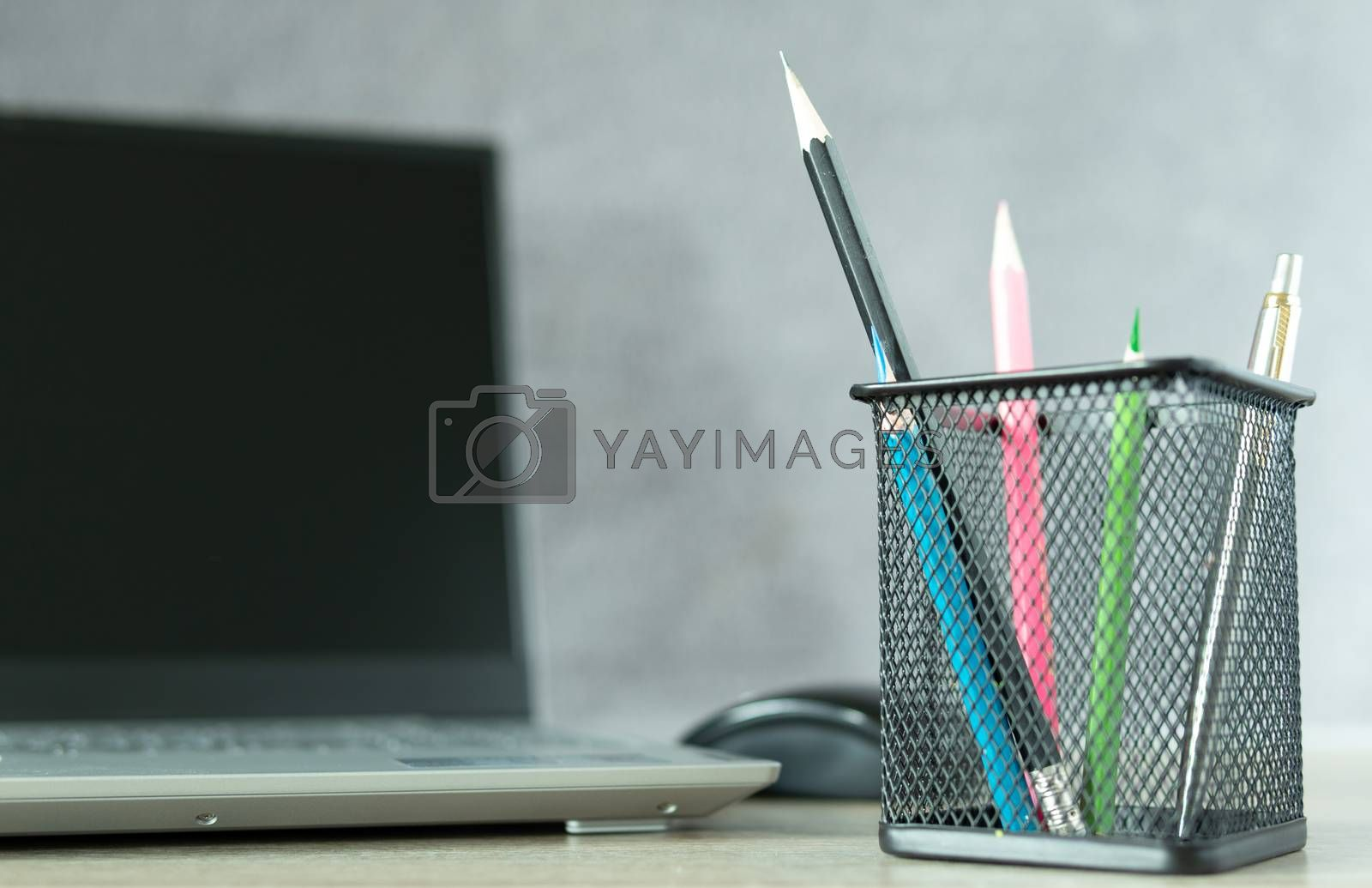 Black basket with blue pencil Ready to use with other colored pencils And notebook computers placed blurred behind on the desk, office equipment at work or at home. Future business concepts