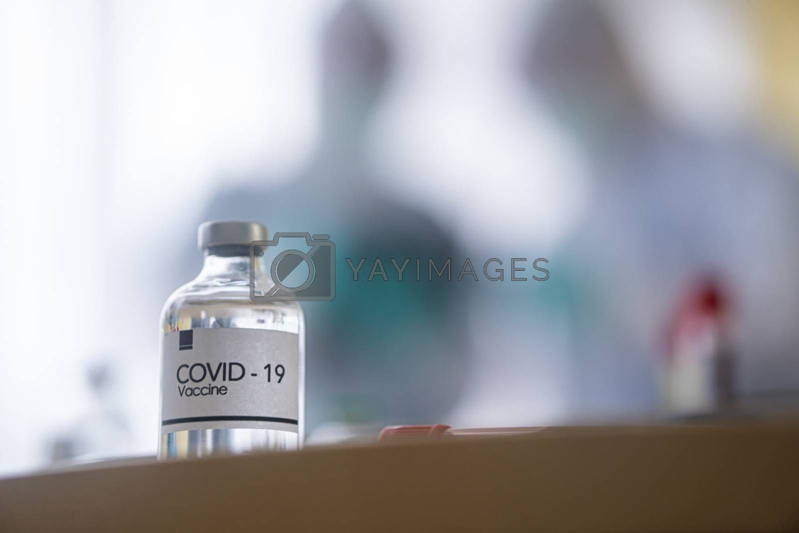 The covid19 doz on the table with blur doctors background. Novel Covid19 vaccine Concept.