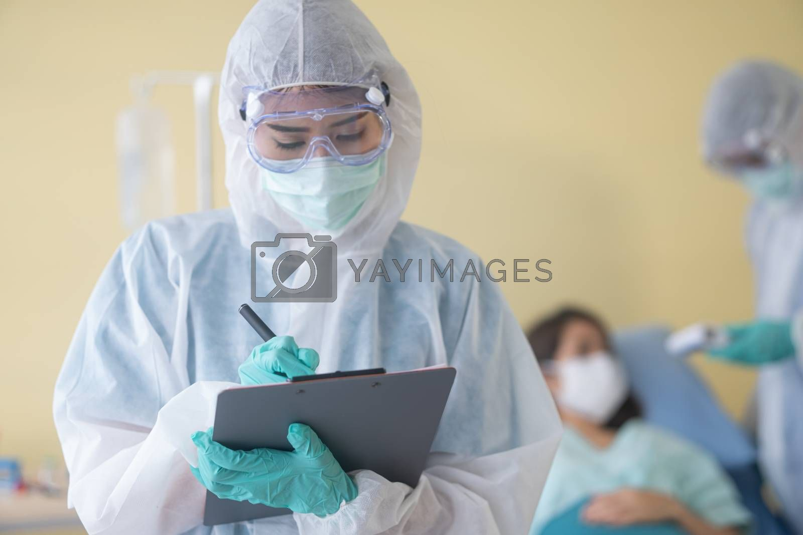 asian woman doctor in personal protective suit or PPE with mask writing on quarantine patient chart, for screening coronavirus. Coronavirus, covid-19 concept.