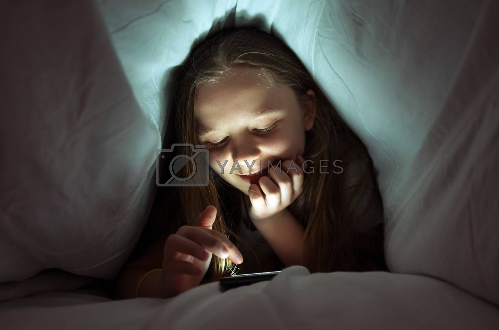 Young girl using a phone in bed by gmstockstudio