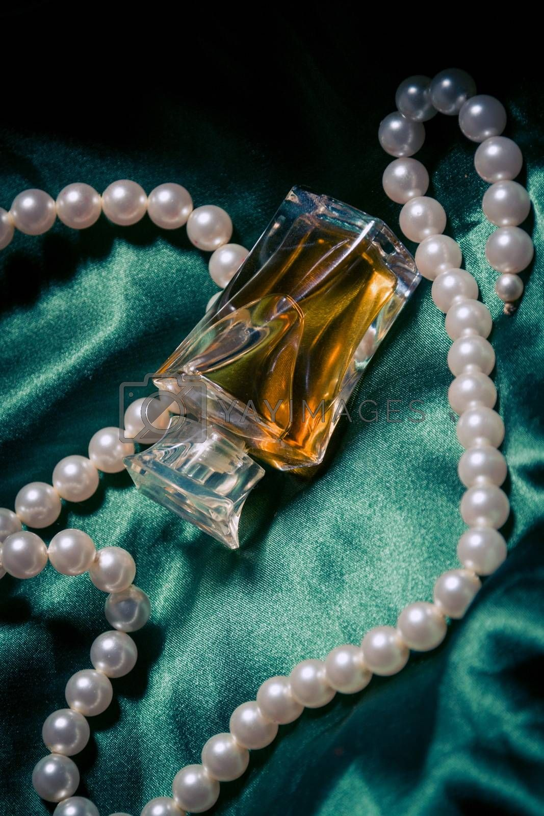 Pearls and perfume closeup on the silk