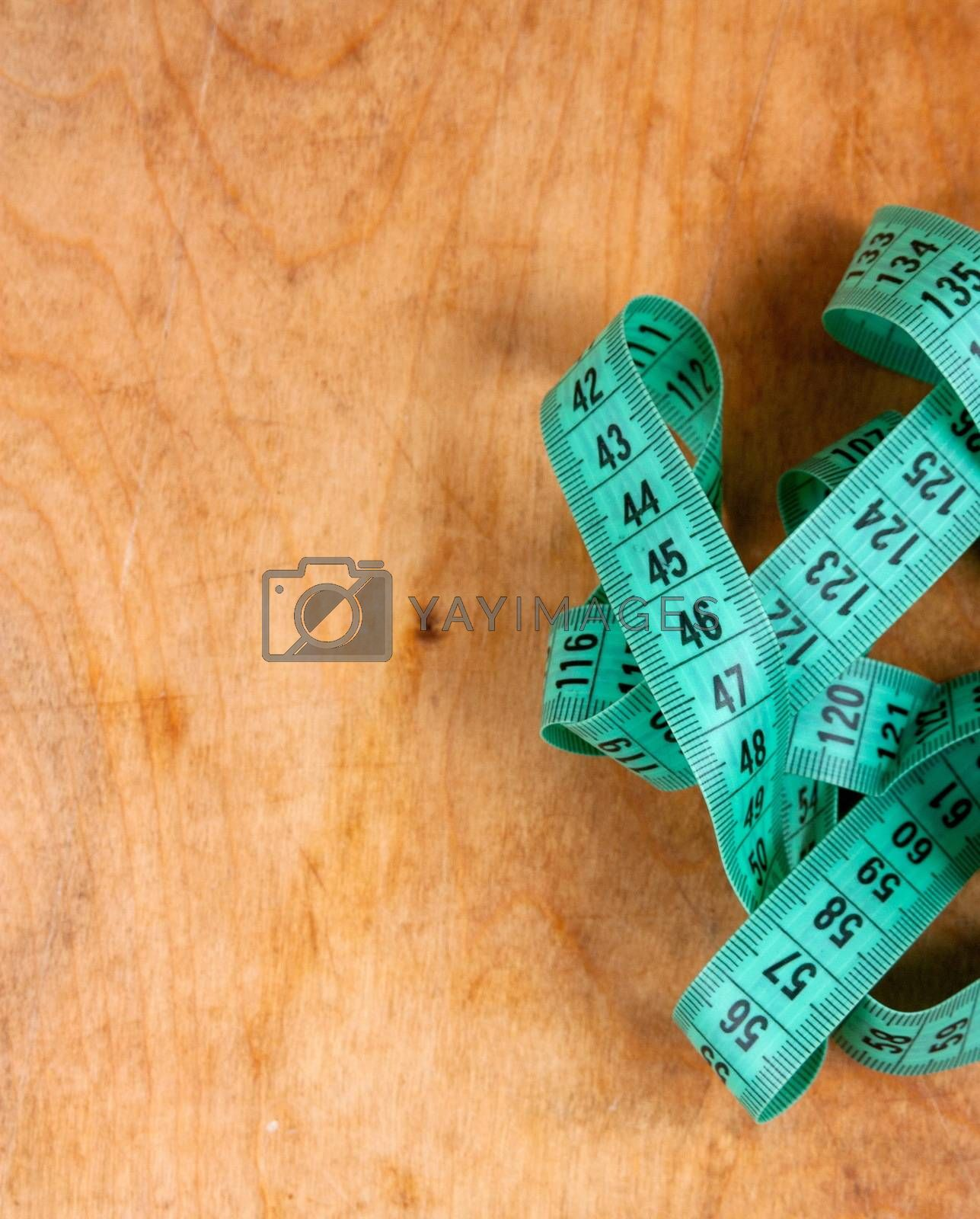 Measuring tape on the wooden background