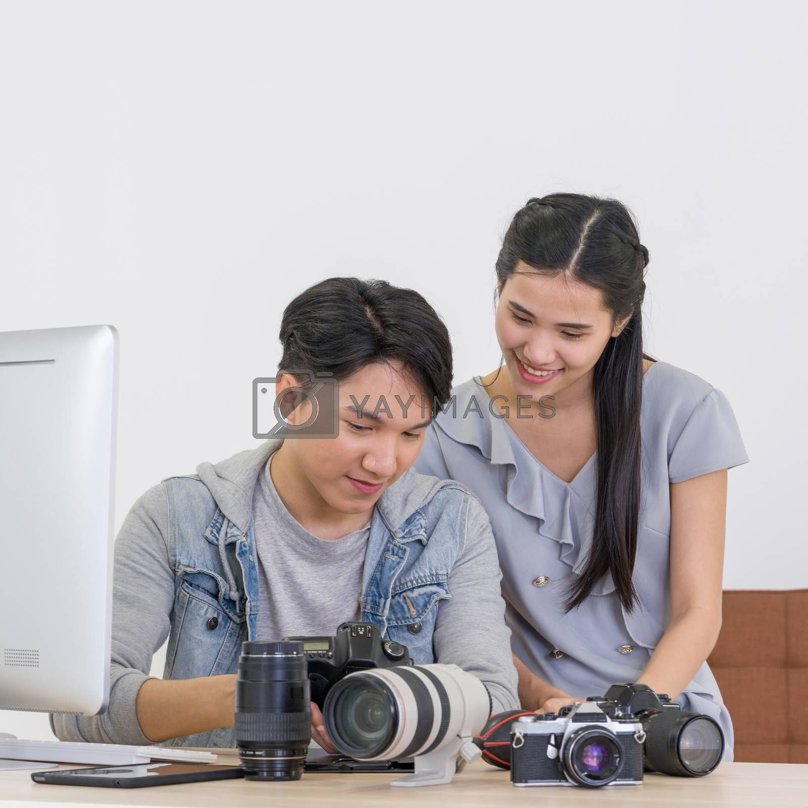 Asian photographer and model looking at pictures taken on the camera screen. The young model is very satisfied with her photo. The atmosphere in the photo studio.