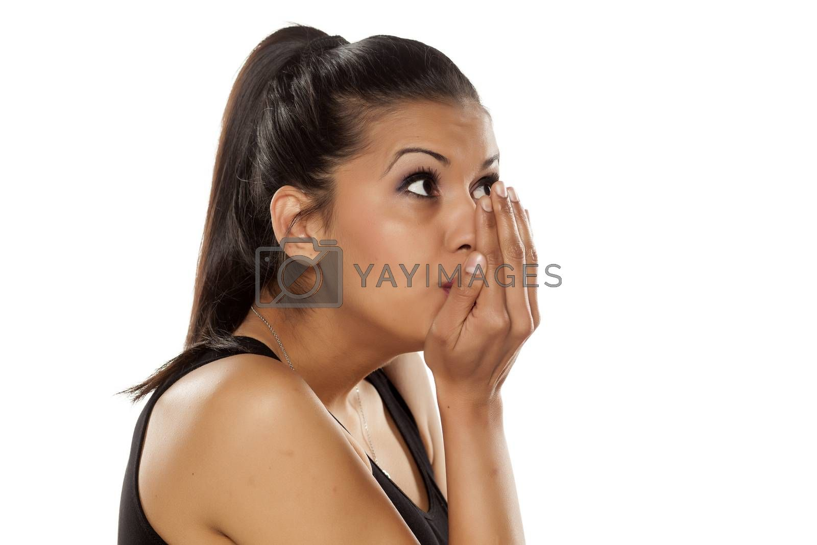 beautiful young woman checking her mouth odor on white background