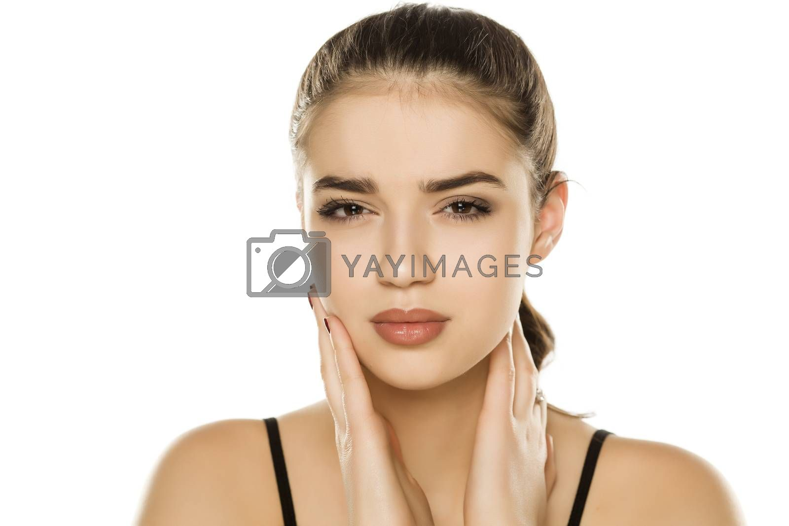 Young beautiful woman with paun in the jaw posing on white background