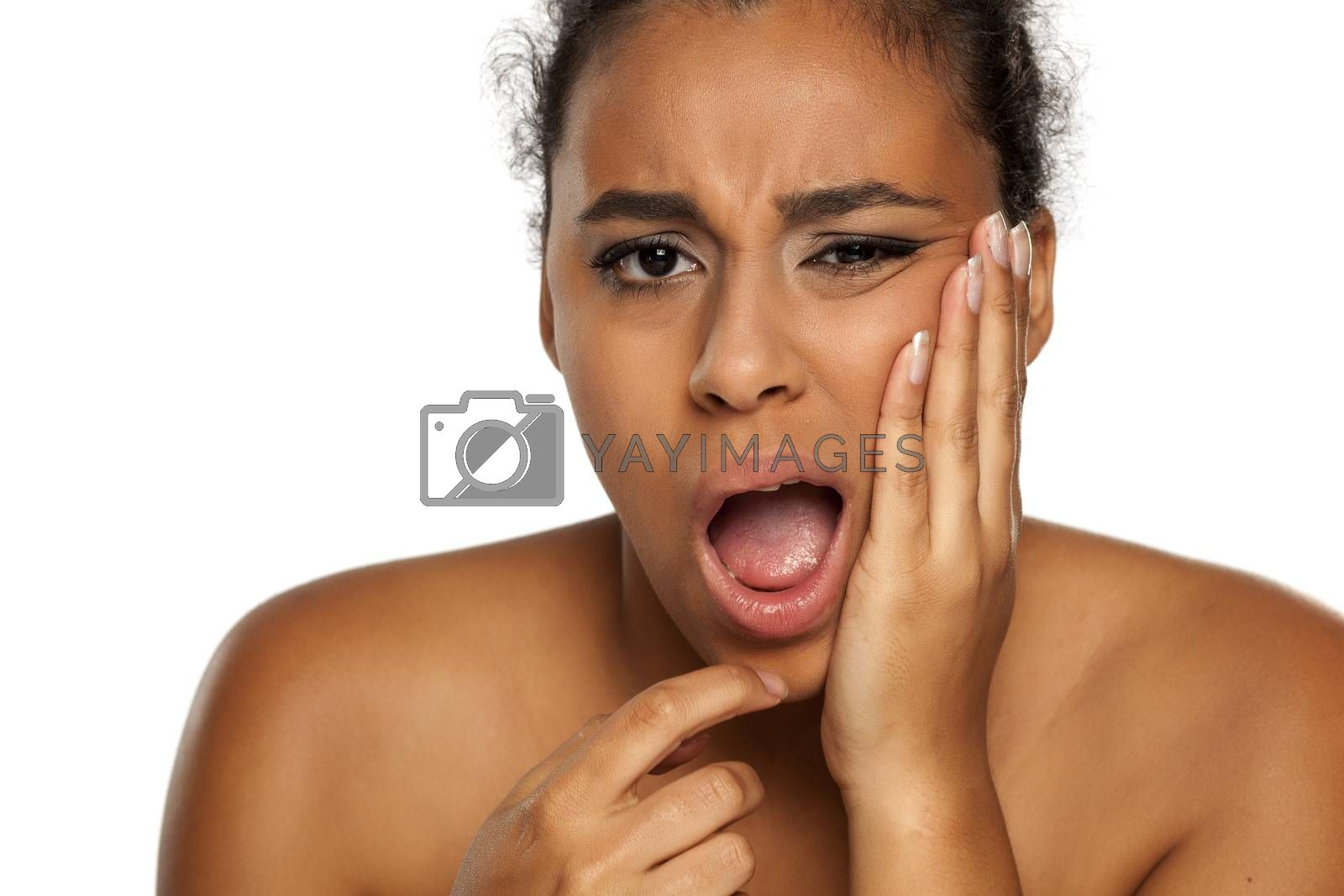 portrait of young dark-skinned woman with tooth ache on white background