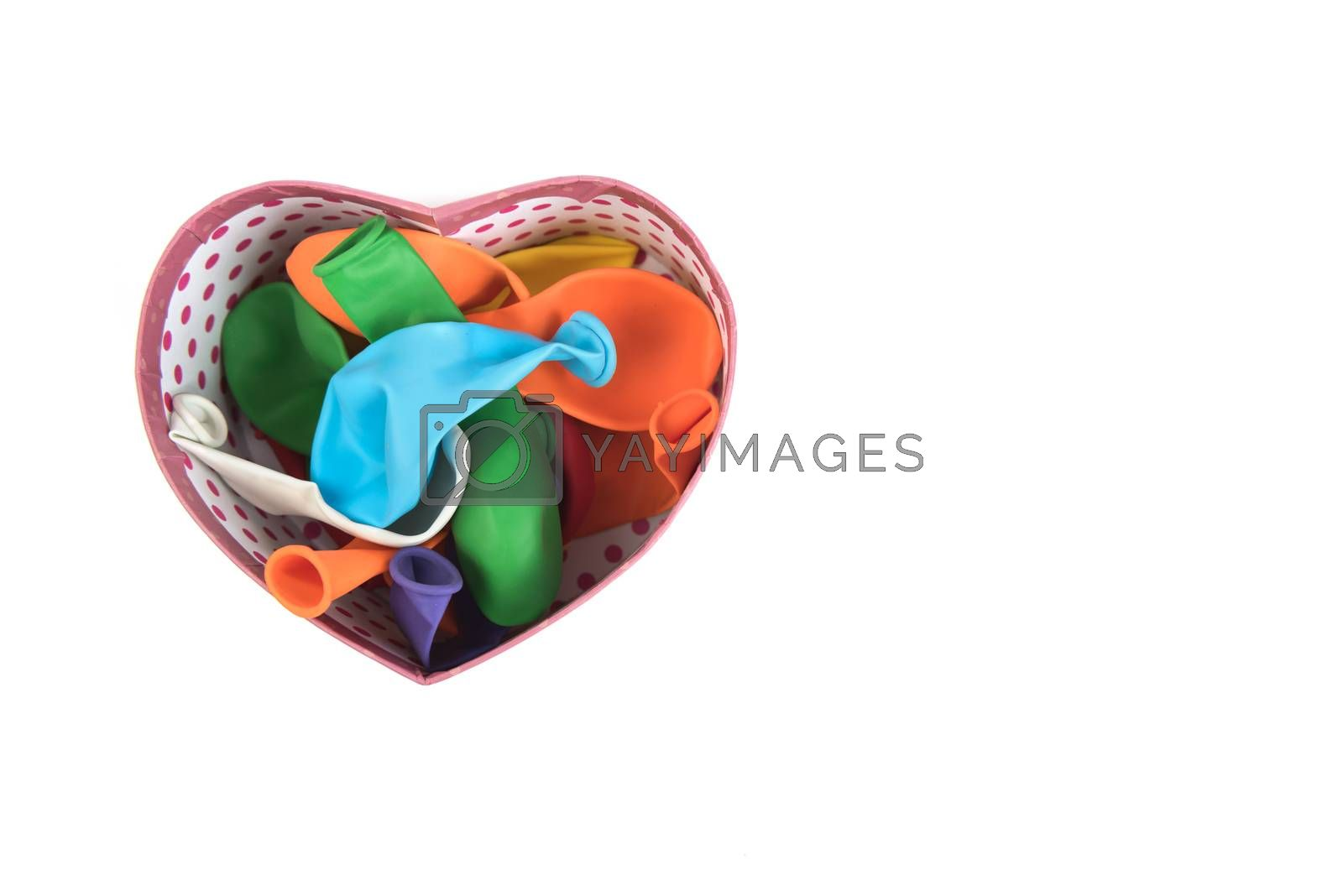 Colorful deflated balloons in heart box on white background