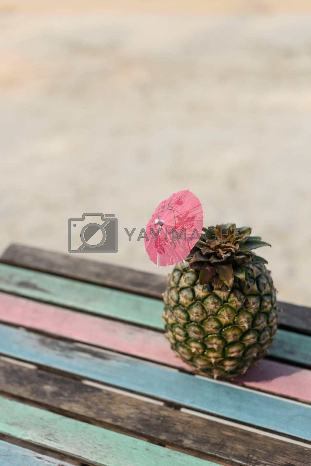 Pineapple fruit on vintage wood table with beach sand background