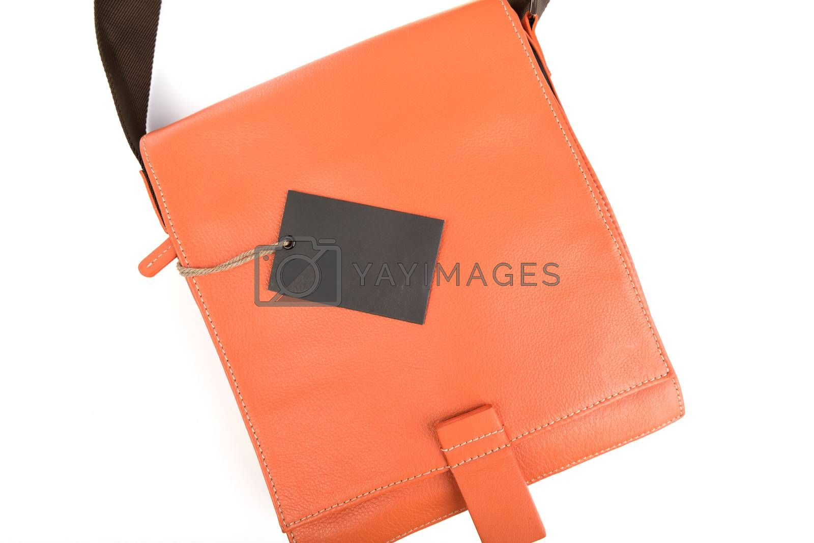 Orange leather bag with black price tag on white background