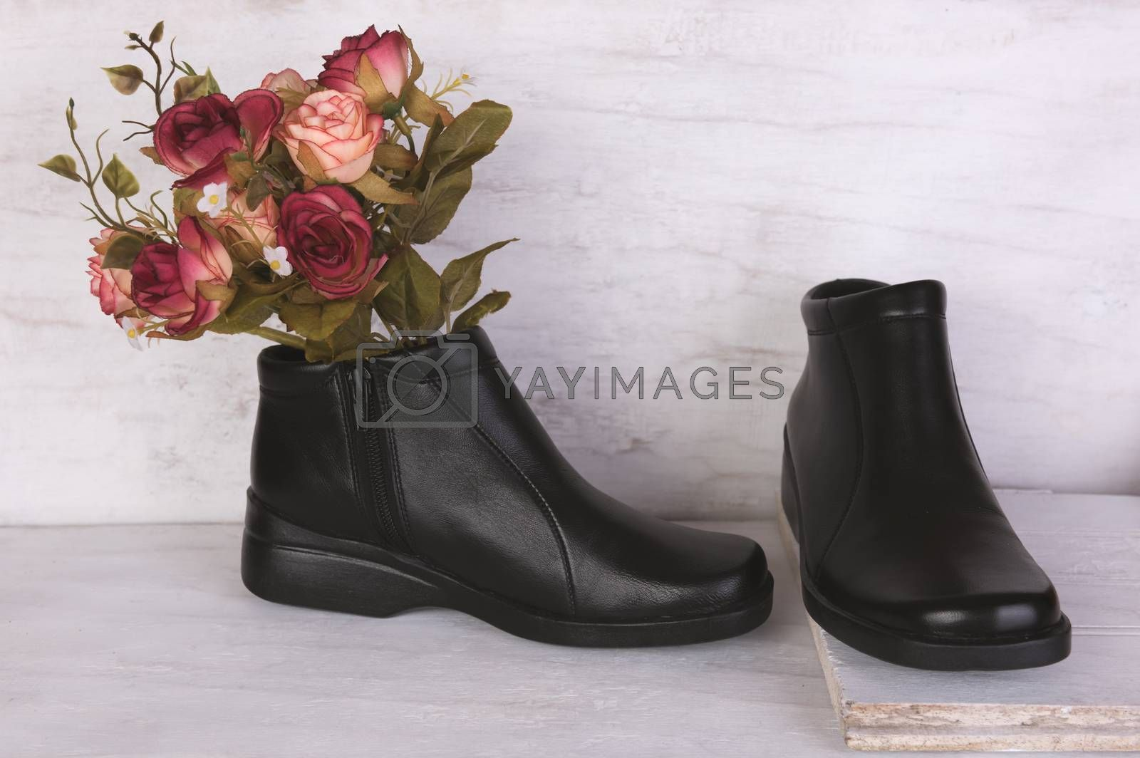 Rose bouquet and black leather shoes on grunge white background