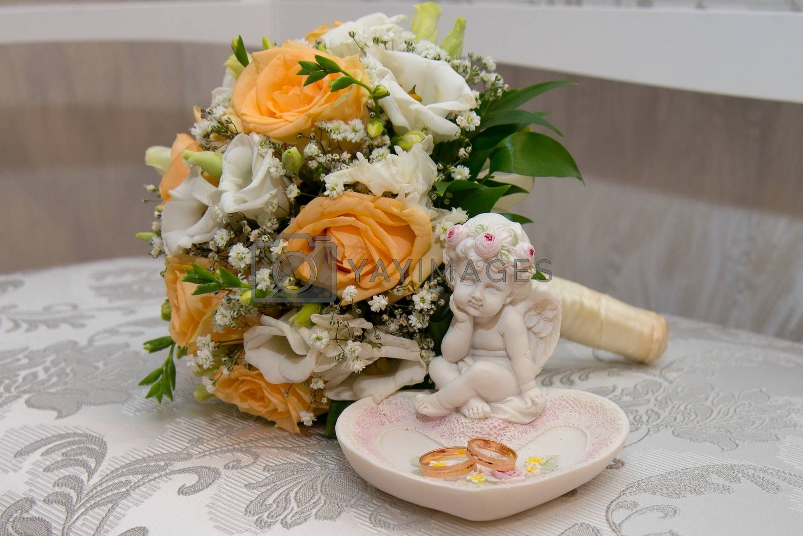 Two beautiful gold wedding rings lie on a platter in a rose shape with the angel sculpture near the bride's bouquet of orange roses and white flowers.