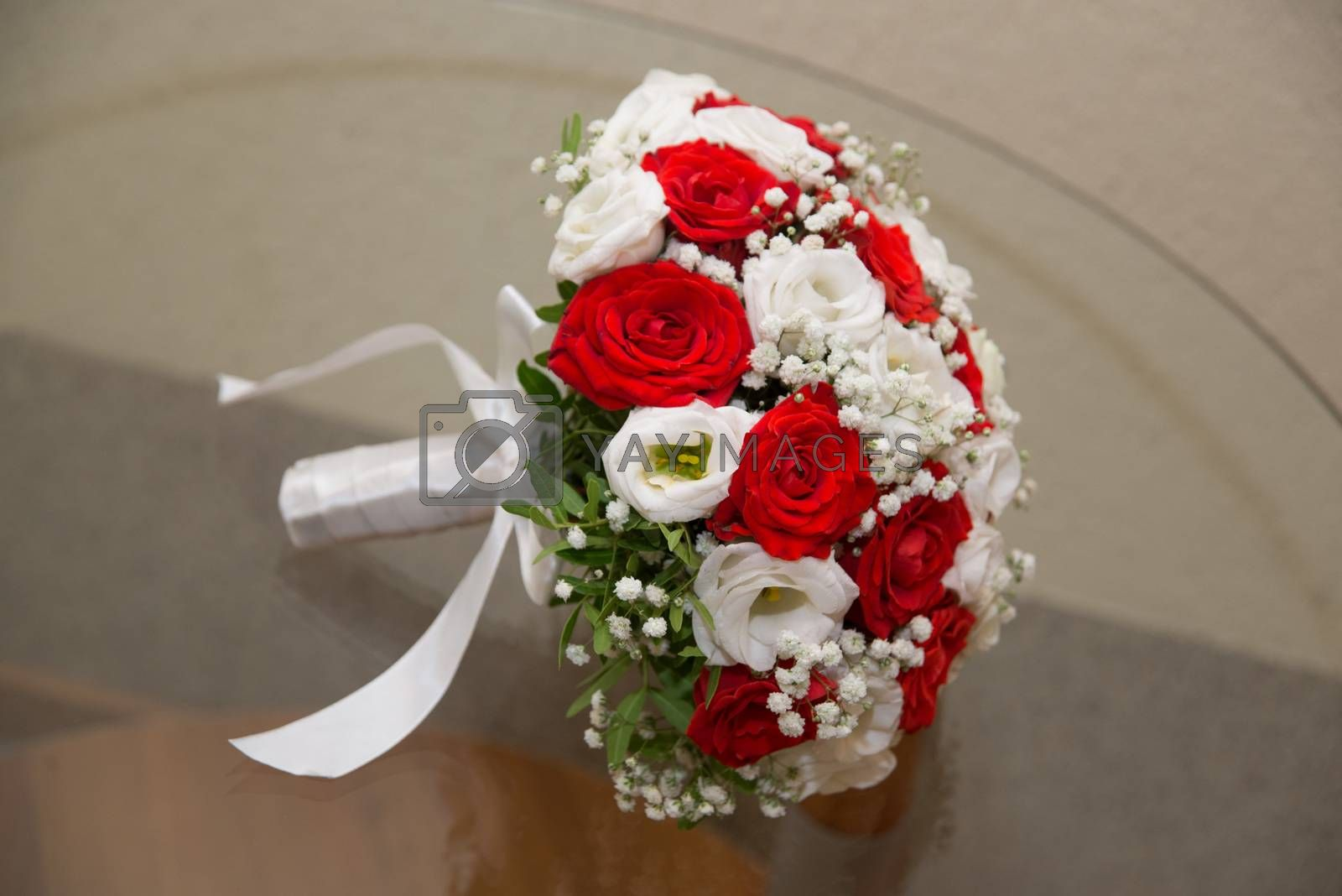 Beautiful wedding bouquet of red and white roses lying on the table.