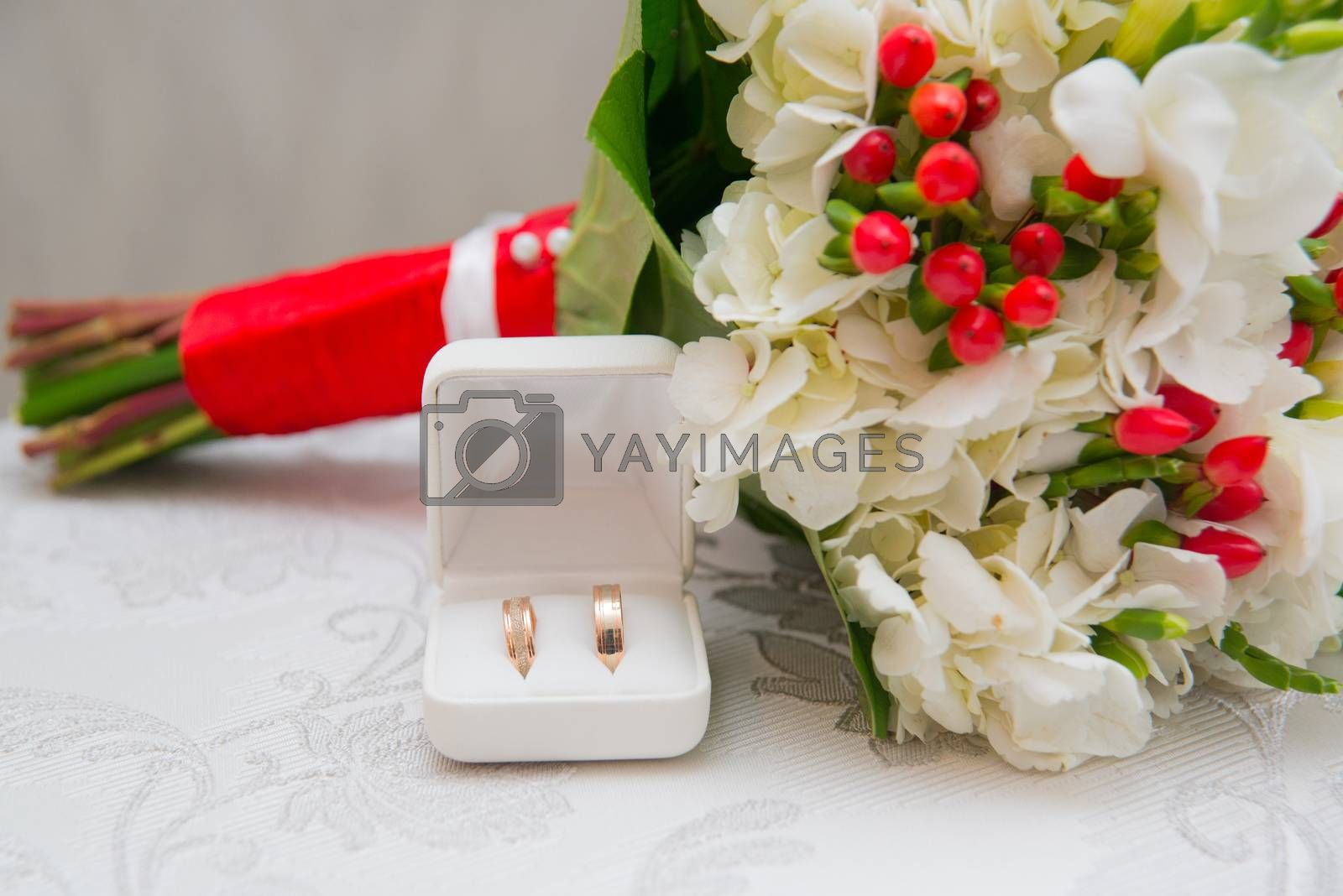 Two Golden wedding rings in white box and bouquet with white flowers and red berries on the table