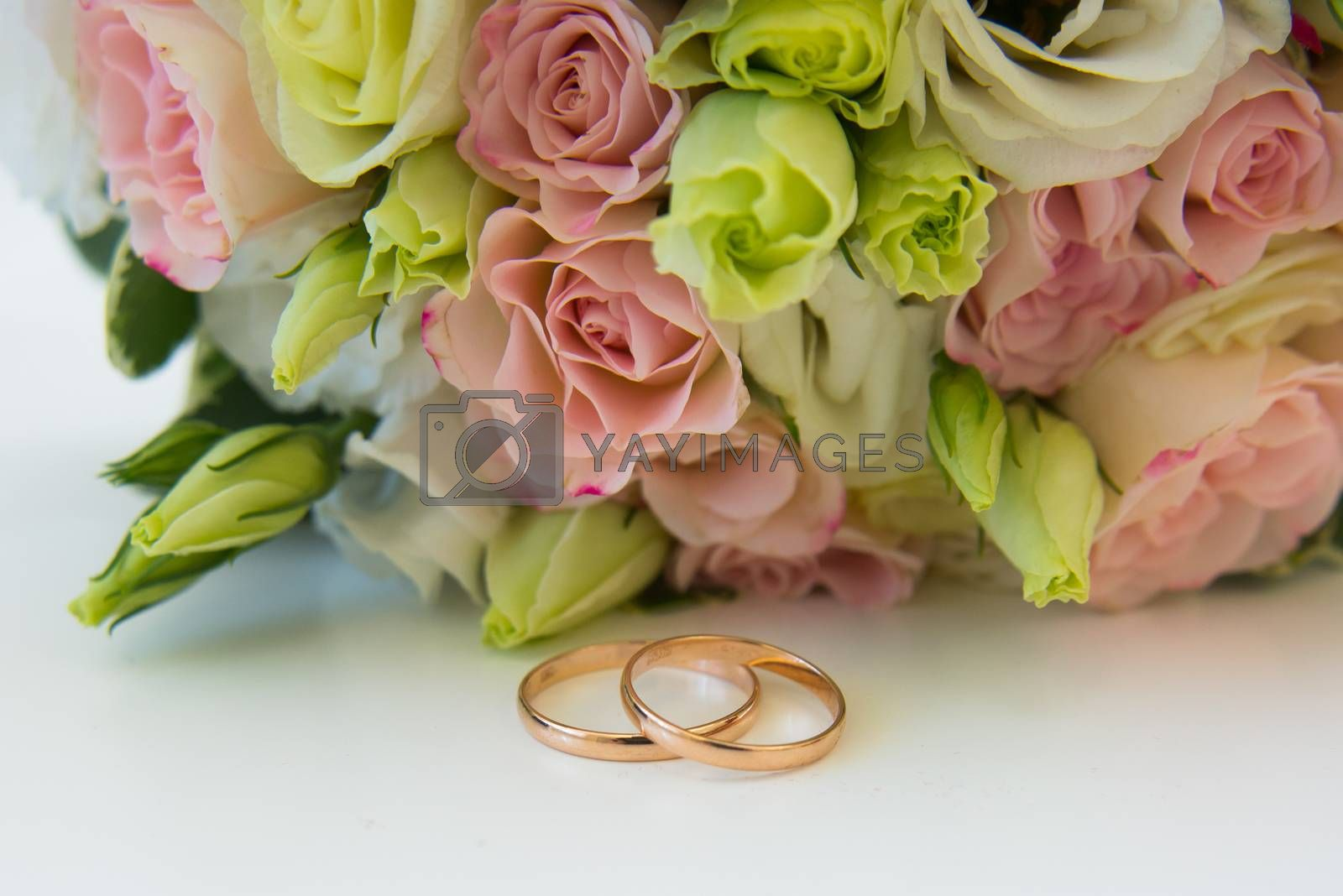Gold wedding rings and flowers. Brides bouquet of pink roses