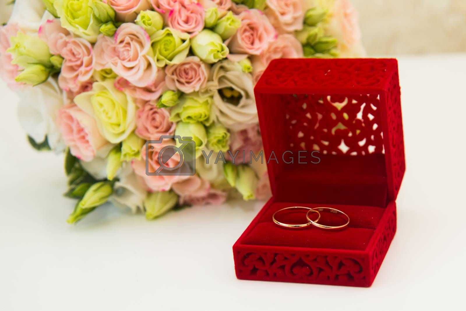Gold wedding ring, a red box and a flower bouquet of the bride on the table