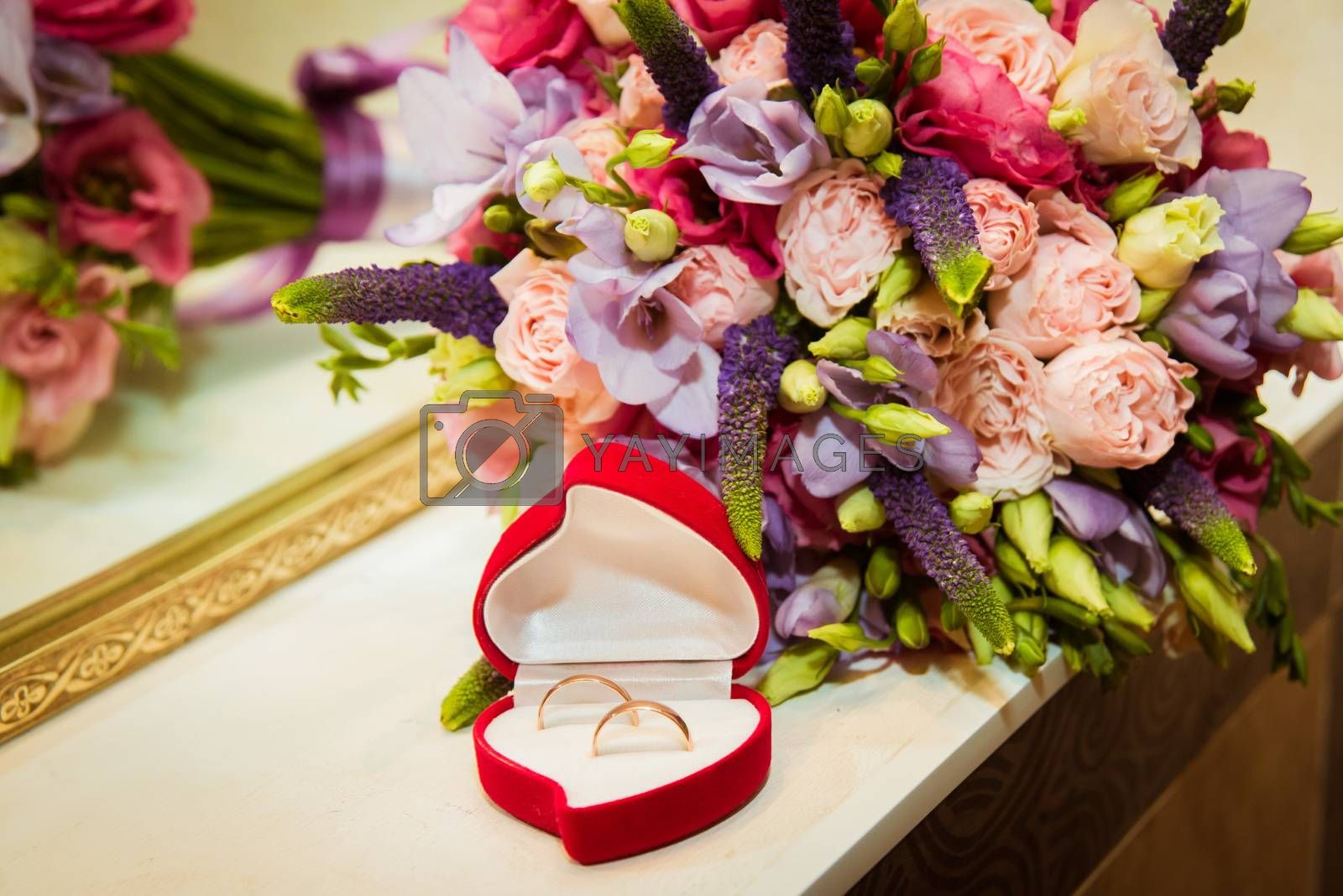 Beautiful Bridal bouquet and two wedding rings in red box in the shape of a heart.