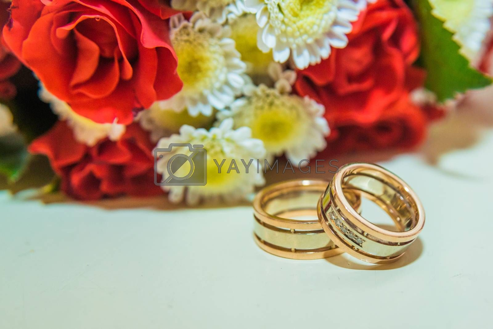 Two gold wedding rings lie and a bouquet of red roses on the table