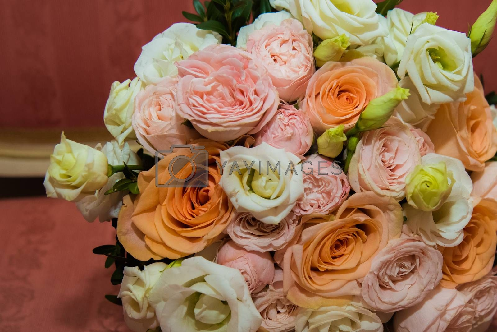 Beautiful wedding bouquet of pink, white, orange roses and green leaves