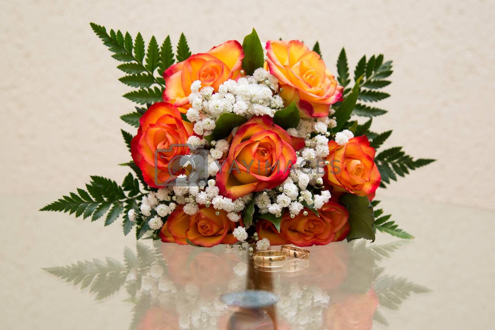 Two beautiful gold wedding rings lie on a bouquet. Orange roses.