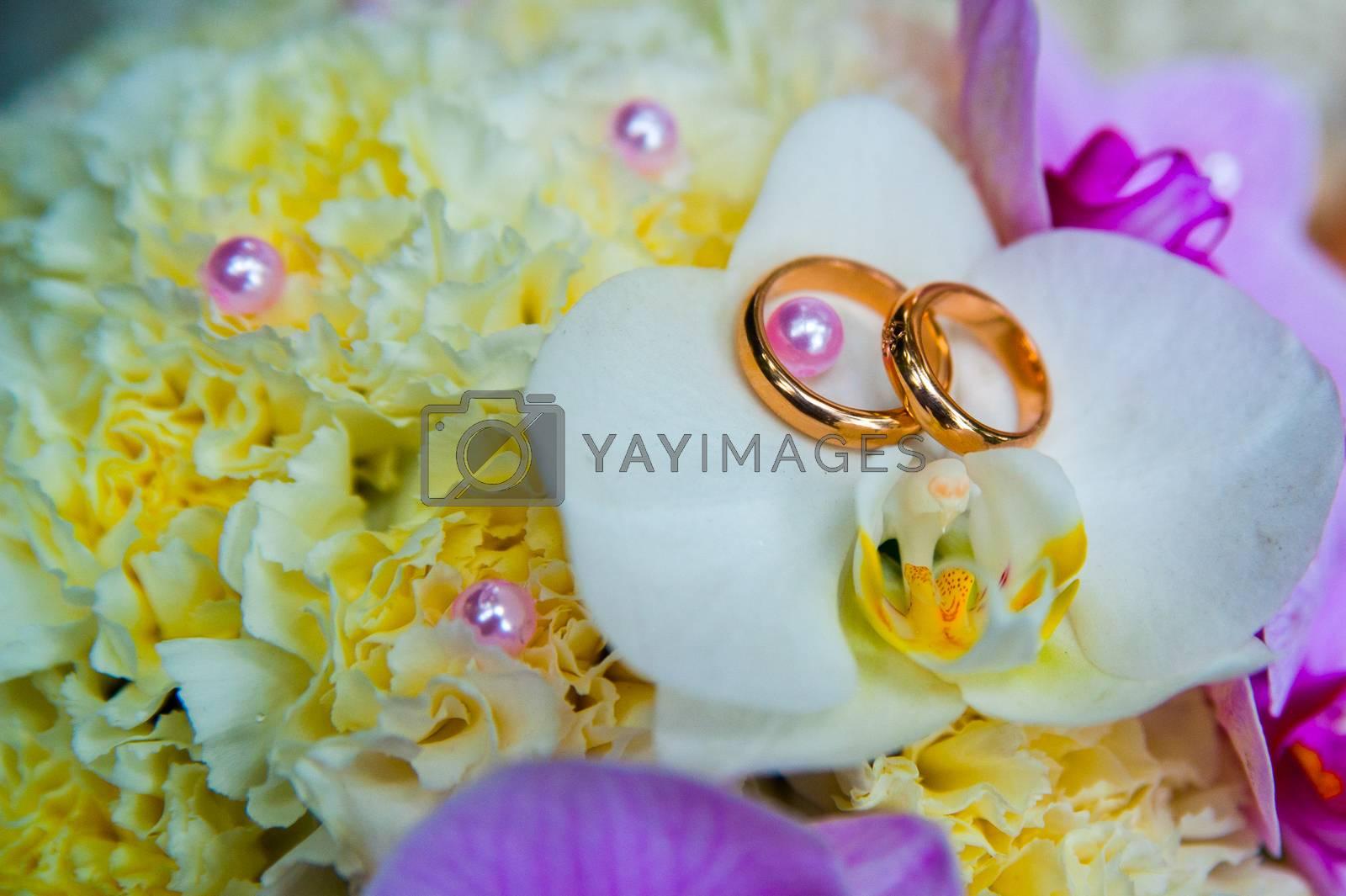 Beautiful gold jewelry lying around flowers. Wedding.Love