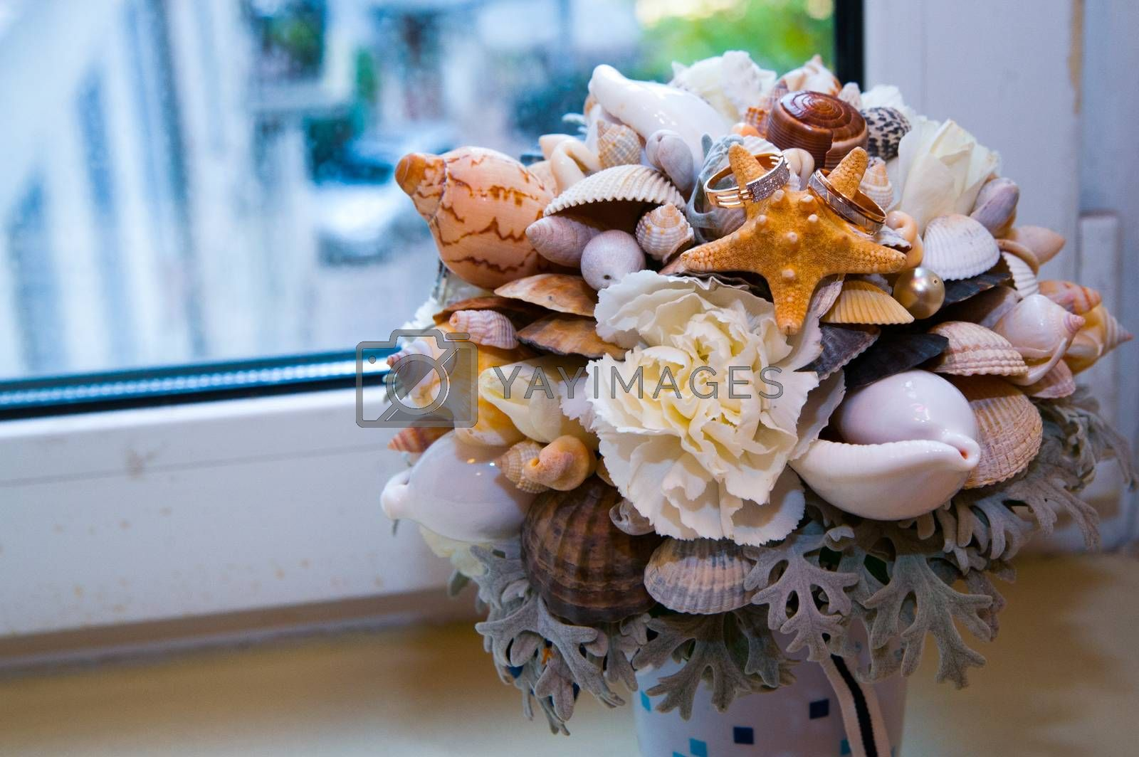 Beautiful gold jewelry lying around flowers in the wedding day