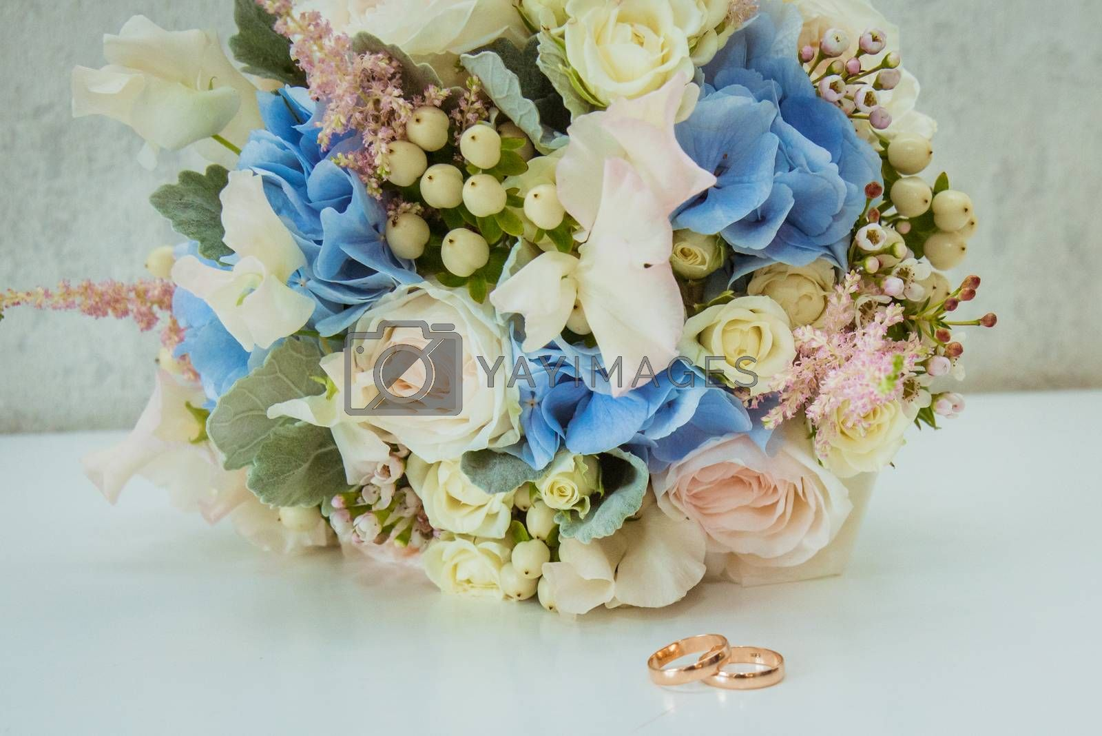 Two Beautiful gold rings of the bride and Groom lie near a bouquet of flowers.
