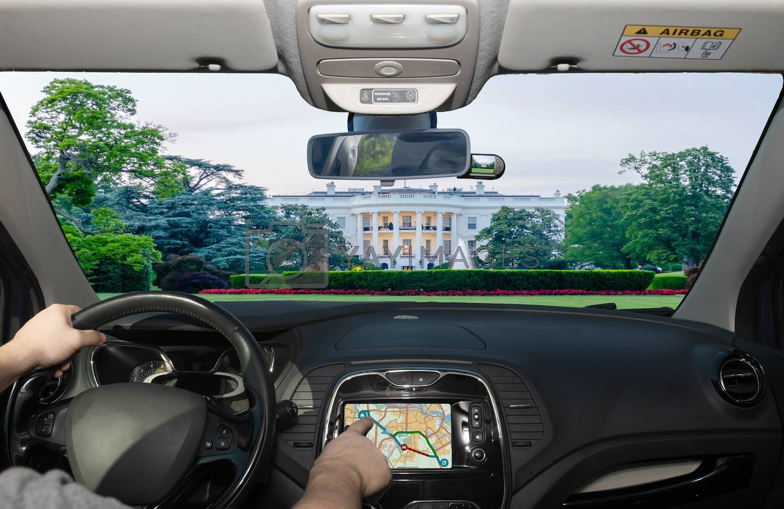 Driving a car while using the touch screen of a GPS navigation system towards the White House, Washington DC, USA