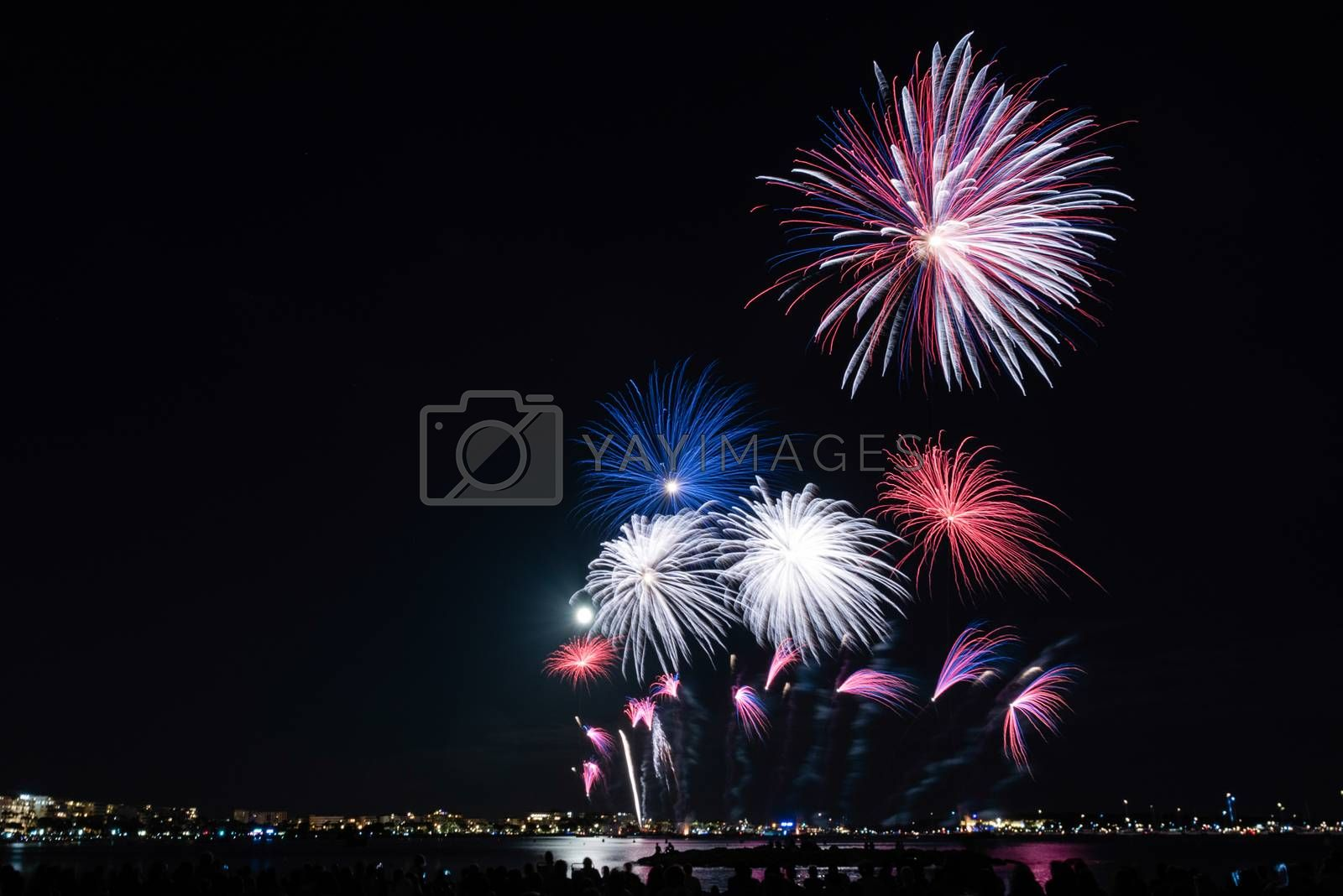 Scenic fireworks glowing in the night for the 14th of July celebrations in the harbor of Cannes, Cote d'Azur, France