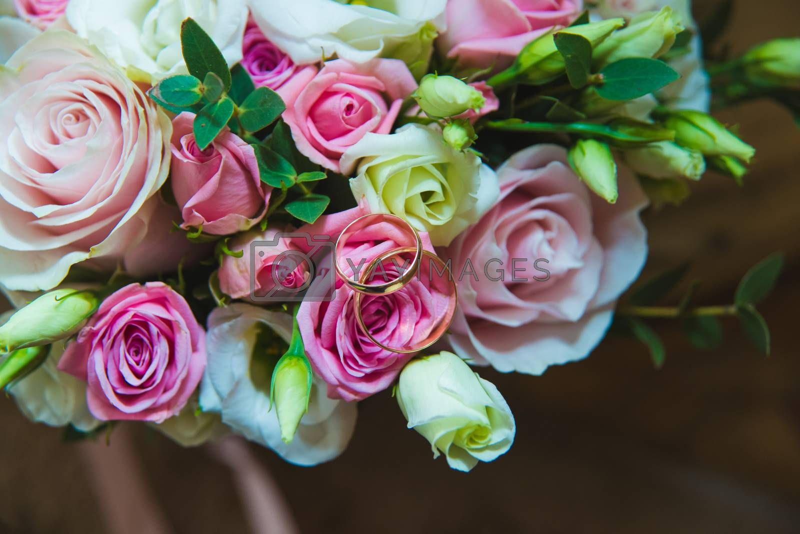 Beautiful delicate wedding bouquet of white roses and wedding rings of the bride and groom. Wedding day.