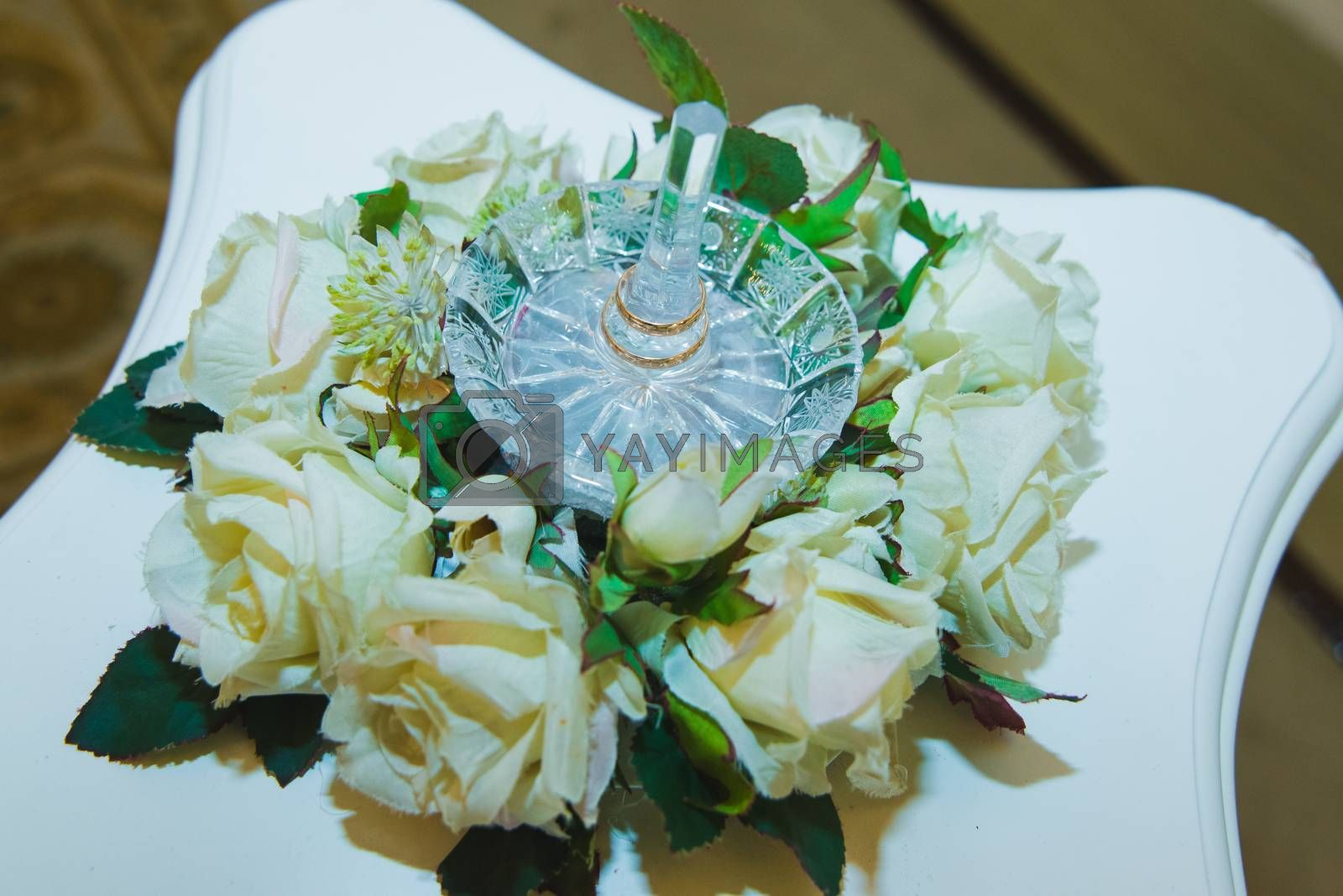Beautiful Wedding rings on a crystal stand of white roses. Wedding day.