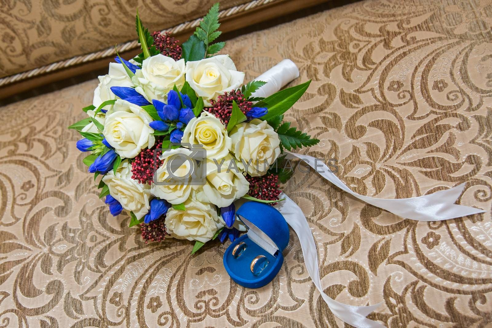 Beautiful delicate wedding bouquet white roses and wedding rings of the bride and groom. Wedding day.