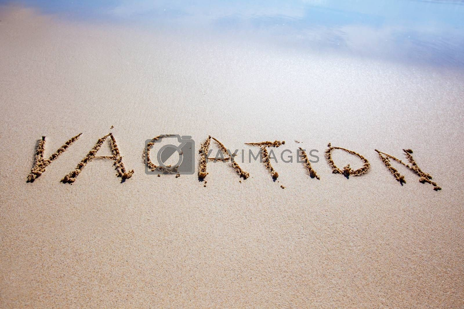Word vacation written in a sandy tropical beach with soft sea wave