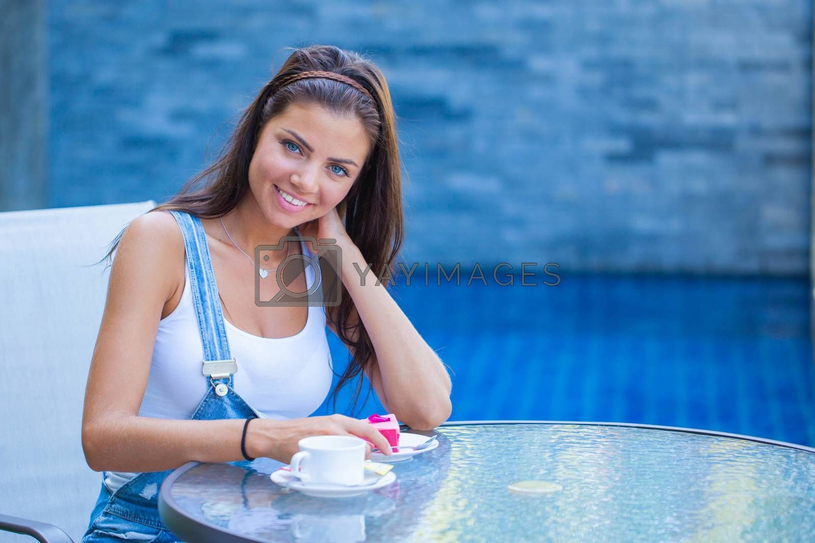 Young woman having a breakfast with coffee and cake sitting outdoors in a cafe and smiling