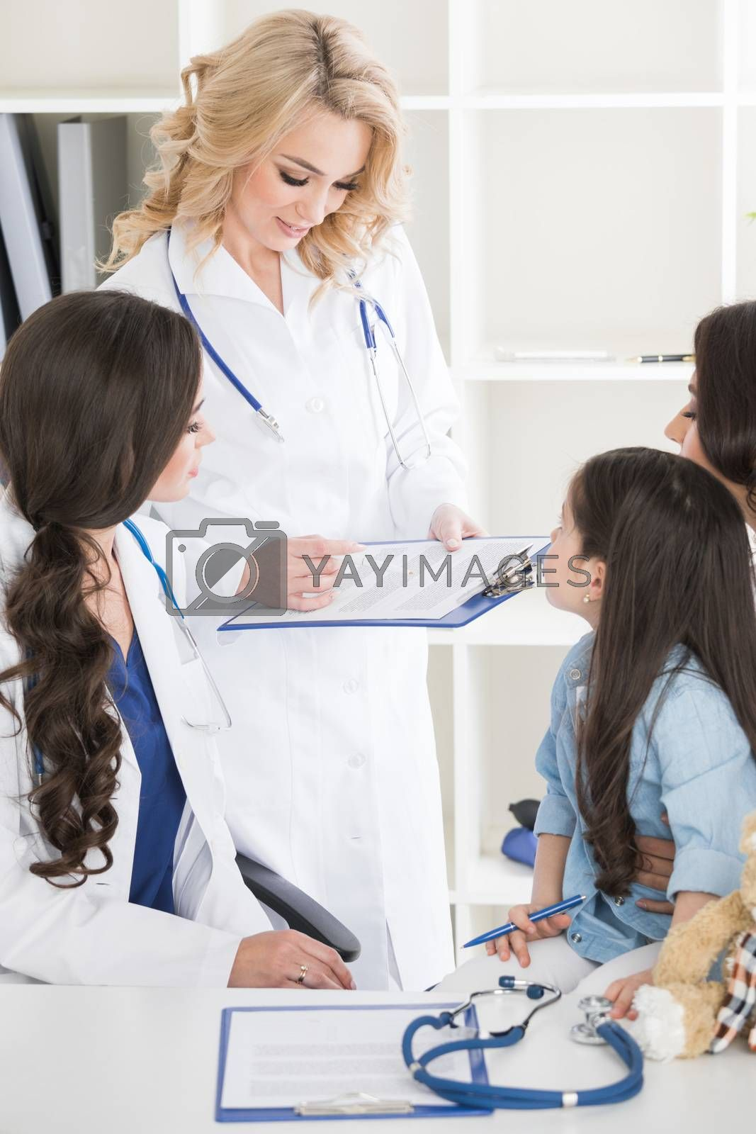 Young mother and girl in pediatrician office, doctor giving diagnosis and prescription