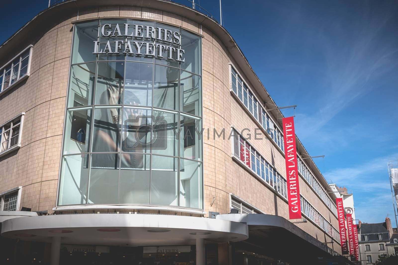 Nantes, France - September 25, 2018: architectural detail of the front of the luxury department store Galeries Lafayette with people walking in the end of the summer