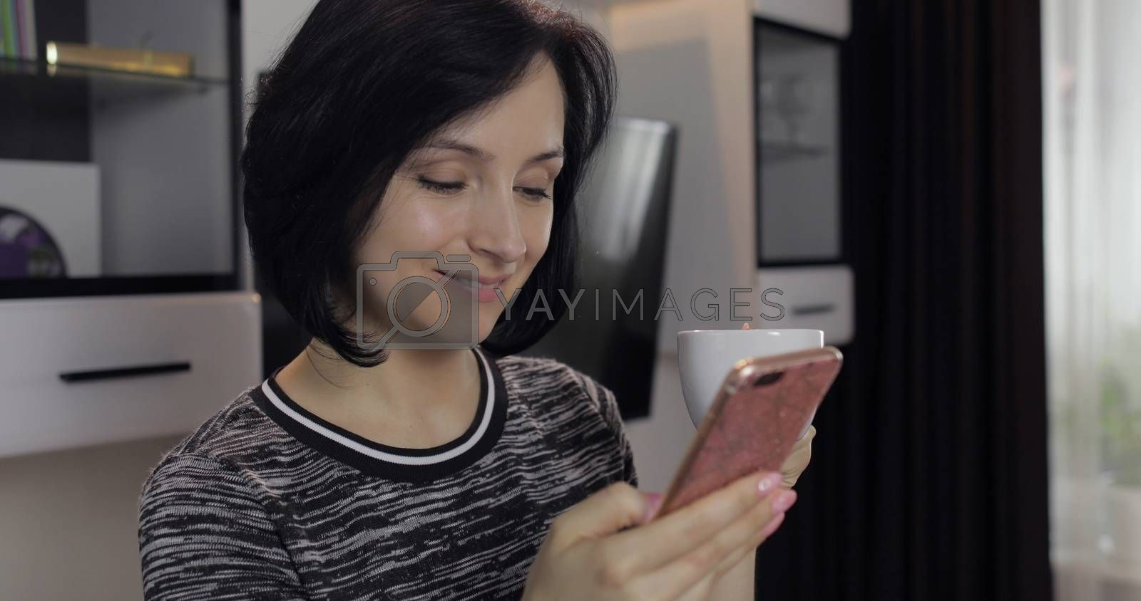 Portrait of pretty caucasian young brunette woman having chat on social media using smartphone enjoying chatting to friend. At home