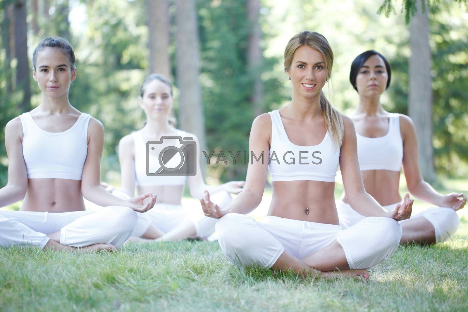 Women in white sportswear sitting in lotus position during group yoga training class at park