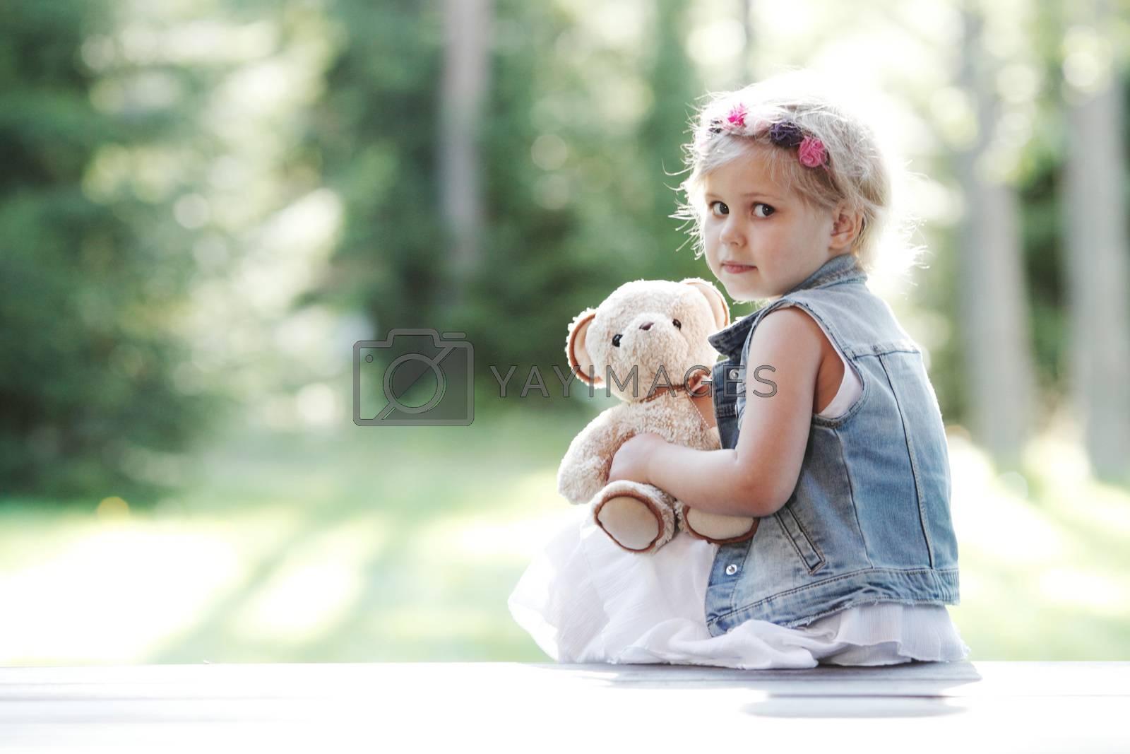 Worried Little girl holding her Teddy bear sitting outdoors