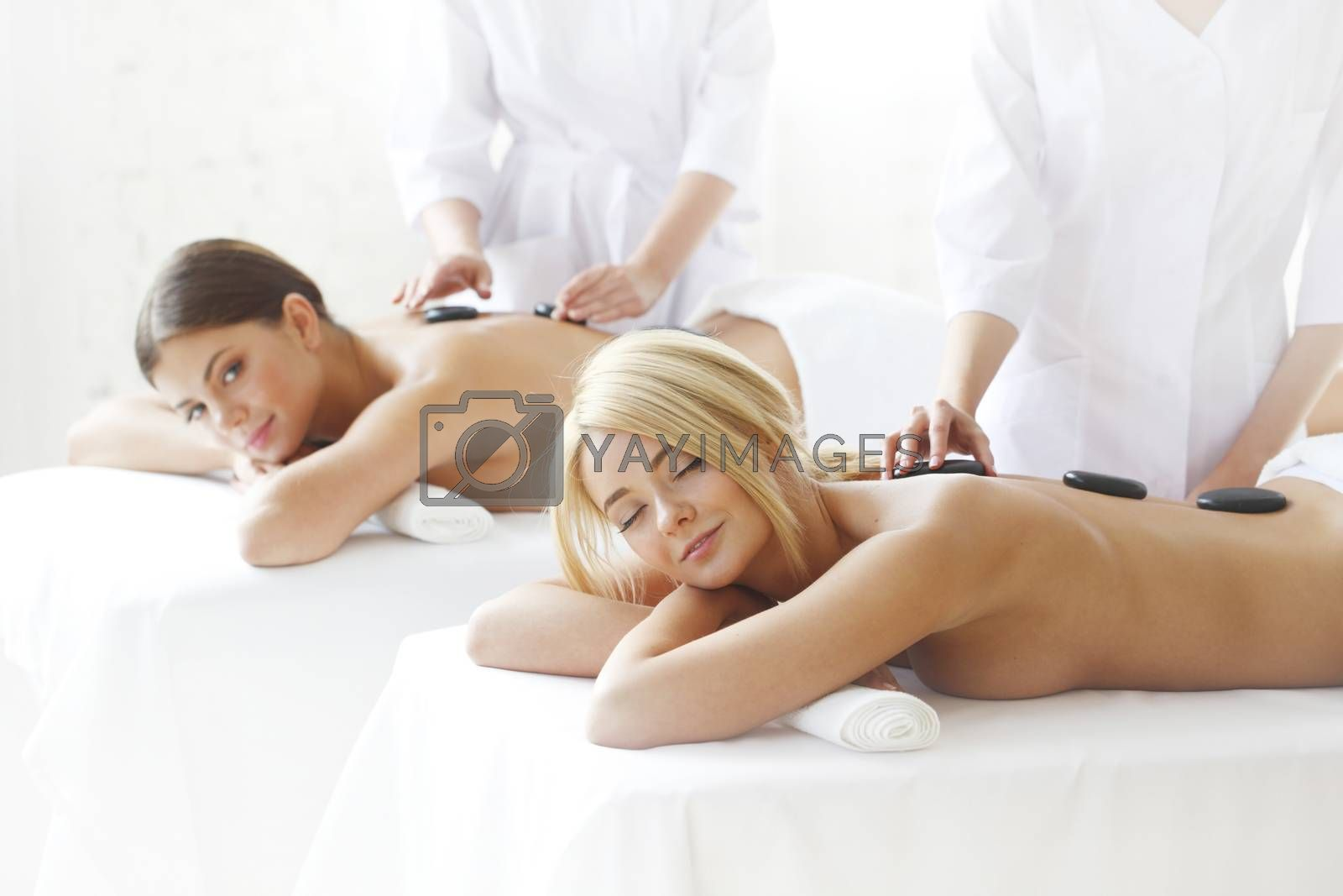 Pretty female friends getting hot stone massage together in the health spa