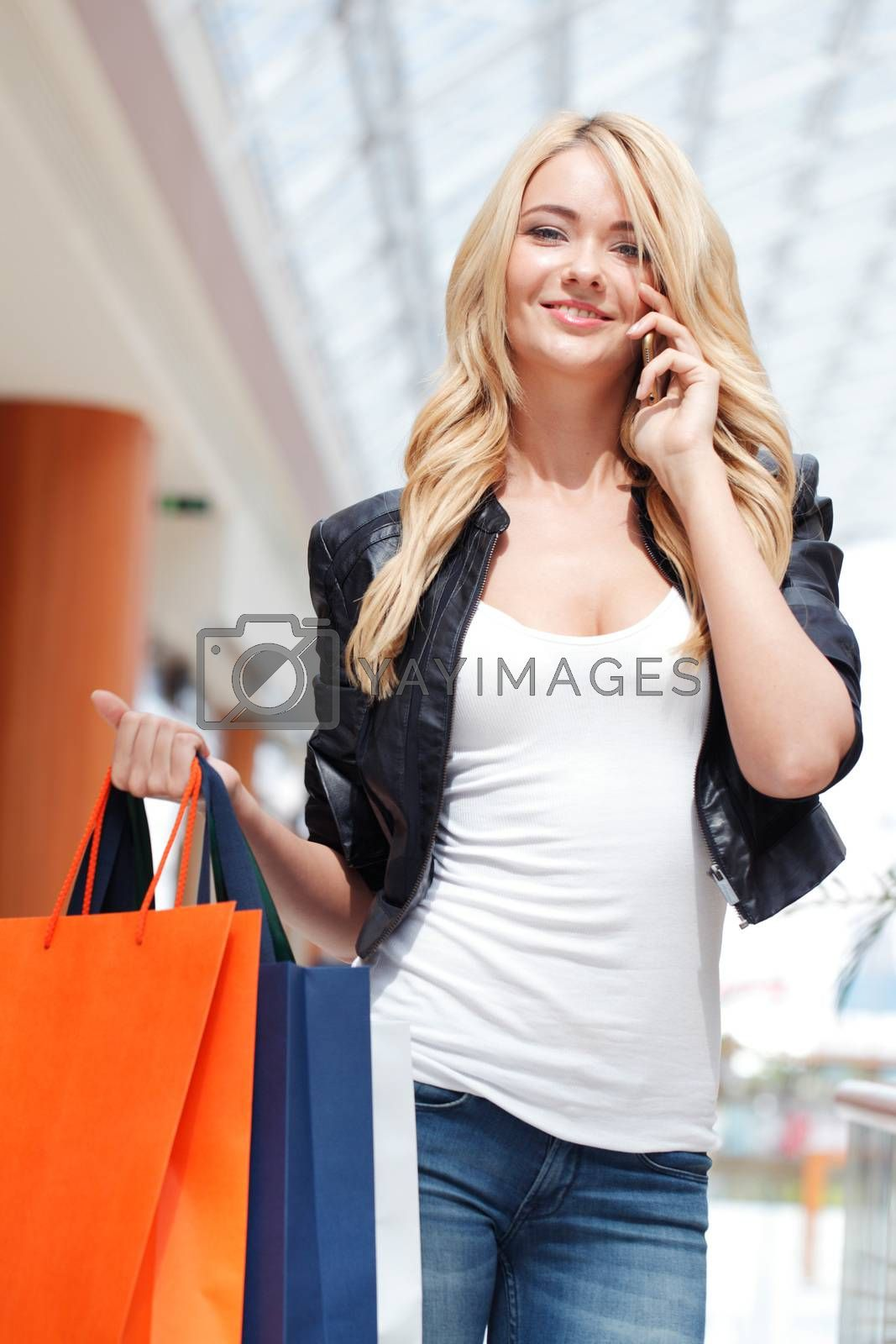 Young beautiful shopping girl with bags talking on the phone in mall
