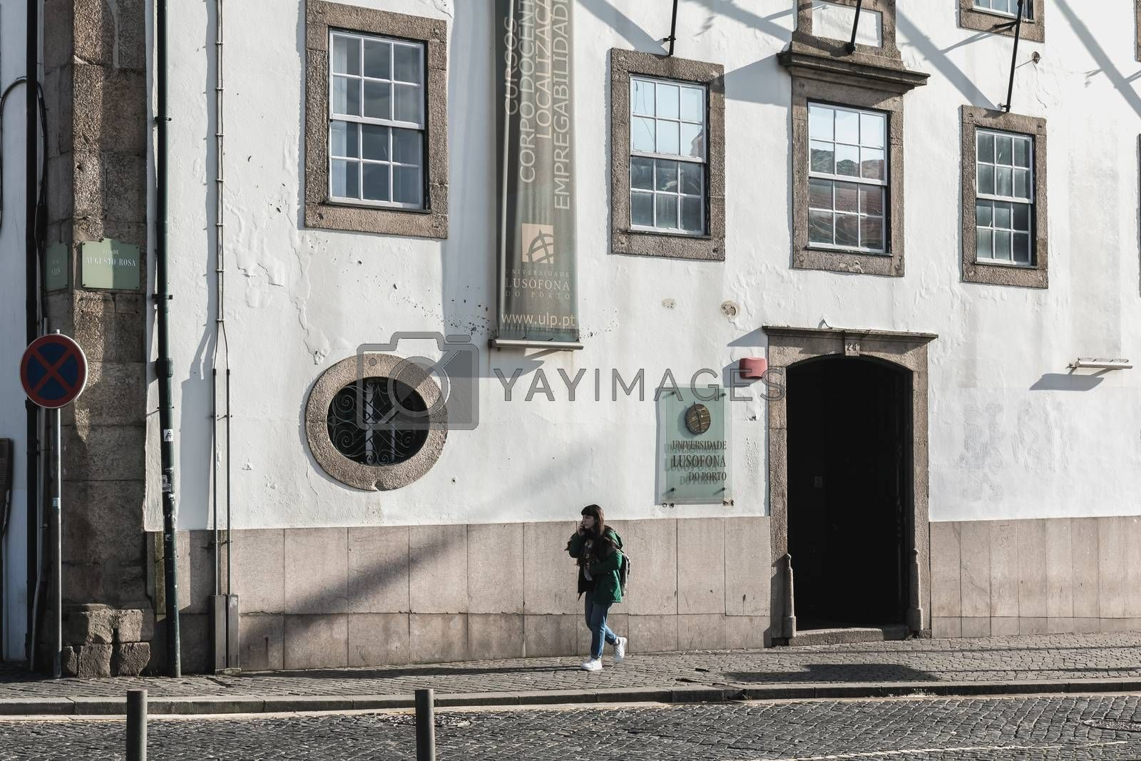 Porto, Portugal - November 30, 2018: Storefront and architectural detail of Lusofona de Porto University in the historic city center where people walk on a winter day