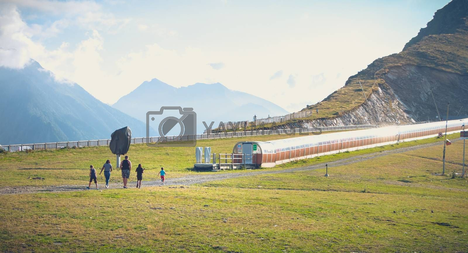 Saint Lary Soulan, France - August 20, 2018: family who walks on the ski slopes of a resort without snow in summer