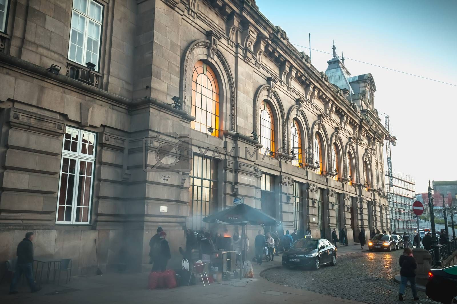 Porto, Portugal - November 30, 2018: Street atmosphere in front of the Porto train station where people walk one autumn evening